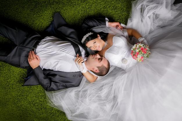 Glimlachende bruid en bruidegom die op het grasachtige tapijt liggen. Premium Foto