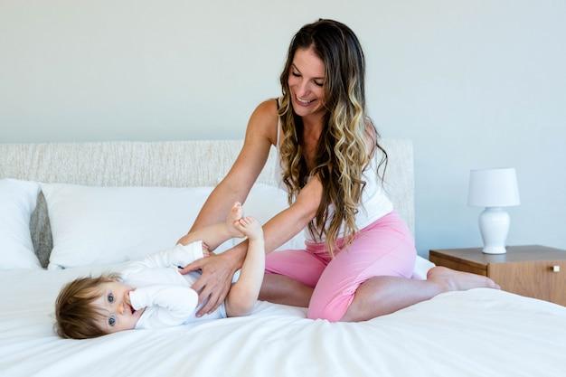 Glimlachende brunette vrouw houdt een schattige baby zittend op een bed Premium Foto