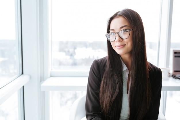 Glimlachende charmante aziatische jonge onderneemster die zich dichtbij het venster bevindt Premium Foto