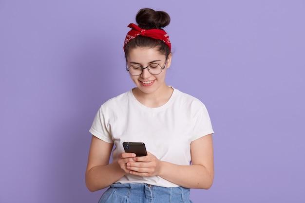 Glimlachende dame met donker haar en knoop die slimme telefoon in handen houdt en bericht van vriend leest, ziet er gelukkig uit, vrijetijdskleding draagt Gratis Foto