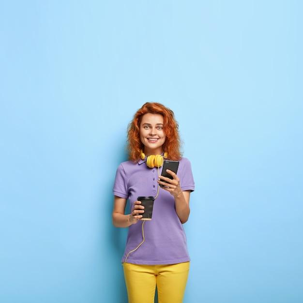 Glimlachende duizendjarige vrouw met golvend rood haar poseren tegen de blauwe muur Gratis Foto