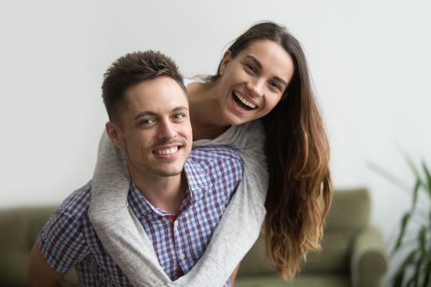 Glimlachende echtgenoot die vrolijke vrouw thuis vervoeren per kangoeroewagen, gelukkig paarportret Gratis Foto
