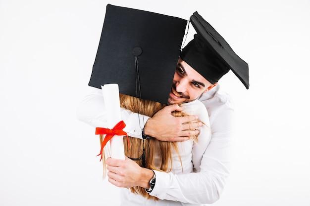 Glimlachende een diploma behalende man die vrouw omhelst Gratis Foto