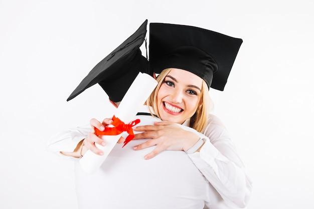 Glimlachende een diploma behalende vrouw die de mens omhelst Gratis Foto