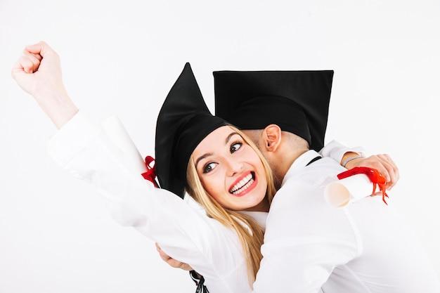 Glimlachende een diploma behalende vrouw die met vriend omhelst Gratis Foto
