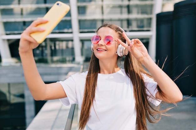 Glimlachende en dansende jonge vrouw die een selfie met haar smartphone maakt en muziek in hoofdtelefoons luistert Gratis Foto