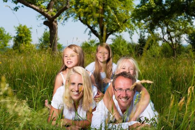 Glimlachende familie die in het gras in de zomer ligt Premium Foto