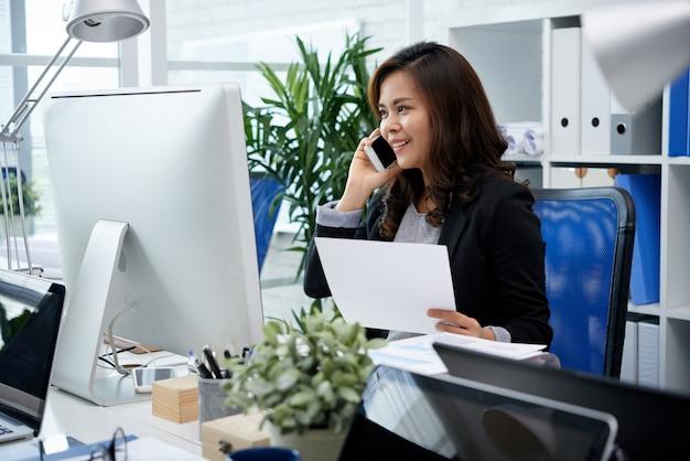 Glimlachende filipijnse onderneemsterzitting bij bureau in bureau en het spreken op mobiele telefoon Gratis Foto