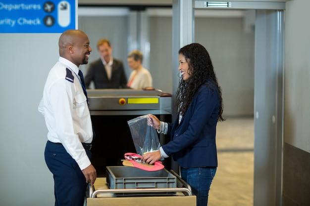 Glimlachende forens die interactie heeft met de beveiligingsbeambte van de luchthaven tijdens het verzamelen van accessoires uit de krat Gratis Foto