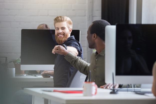 Glimlachende gebaarde mens die een vuistbuil geeft aan een mannelijke collega Gratis Foto