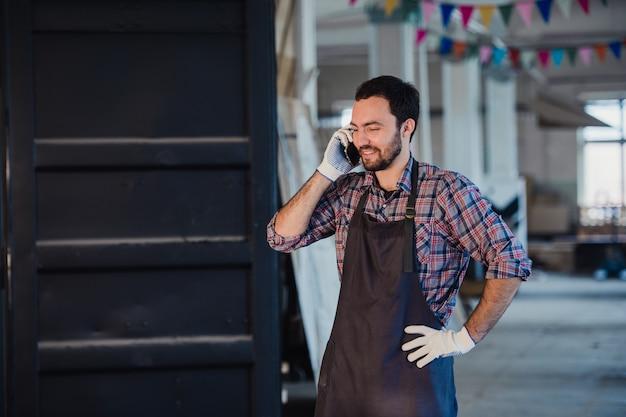 Glimlachende gebaarde mens die handschoenen, eigenaar van een klein houtbewerkingsbedrijf dragen, die zich in zijn workshop bevinden, die op mobiele telefoon spreken Premium Foto