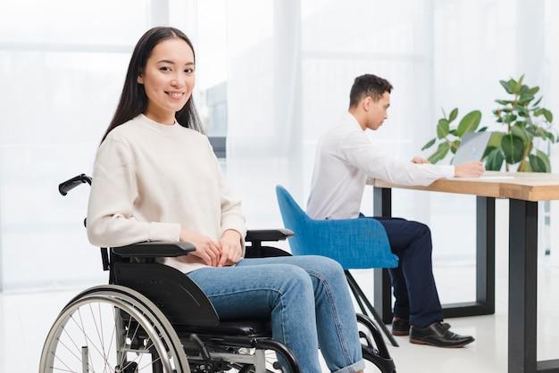 Glimlachende gehandicapte jonge vrouwenzitting op rolstoel die camera voor de mens bekijken die aan laptop werken Gratis Foto