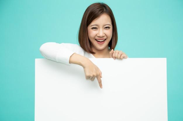Glimlachende gelukkige aziatische vrouw die zich achter grote witte affiche bevinden en vinger neer richten aan lege copyspace die op lichtgroen wordt geïsoleerd Premium Foto