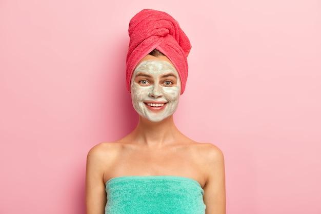 Glimlachende gelukkige jonge vrouw geldt voedende zelfgemaakte klei masker op gezicht, verwent de huid, gewikkeld in een zachte handdoek, geeft om teint, heeft natuurlijke schoonheid, modellen binnen Gratis Foto