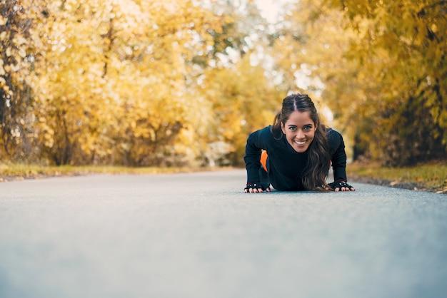 Glimlachende geschiktheidsvrouw die opdrukoefeningen in stadspark doen. Premium Foto