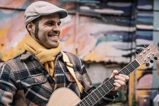 Glimlachende gitaristmens die op de straat spelen Premium Foto