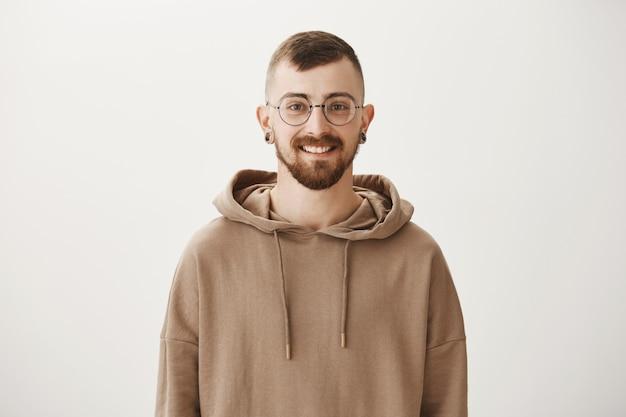 Glimlachende hipster kerel in glazen en hoodie op zoek gelukkig Gratis Foto