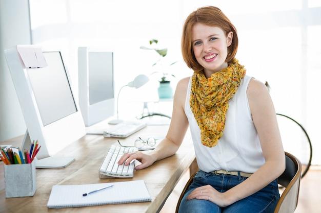 Glimlachende hipster zakenvrouw zit aan haar bureau, draagt een sjaal Premium Foto