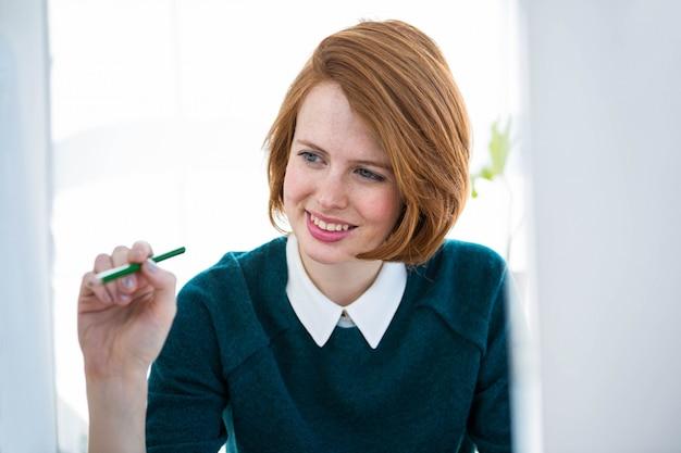 Glimlachende hipster zakenvrouw, zittend aan haar bureau, kijkend naar haar computer Premium Foto