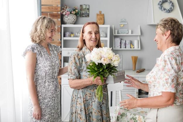 Glimlachende hogere de bloemboeket en gift die van de vrouwenholding zich met haar dochter en kleindochter bevinden Gratis Foto