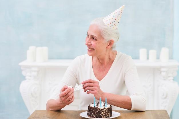 Glimlachende hogere verjaardagsvrouwenzitting dichtbij de deelhoorn van het cakelenigte Gratis Foto
