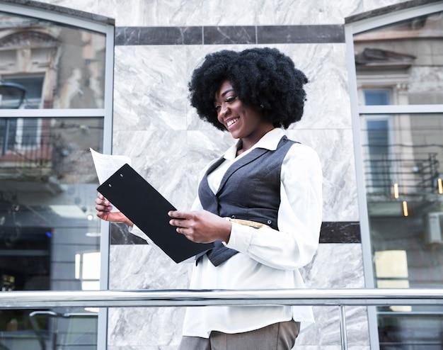 Glimlachende jonge afrikaanse jonge onderneemster die het document op klembord controleert Gratis Foto