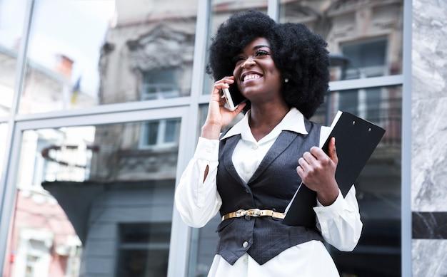 Glimlachende jonge afrikaanse onderneemster die op mobiele telefoon voor glasdeur spreekt Gratis Foto