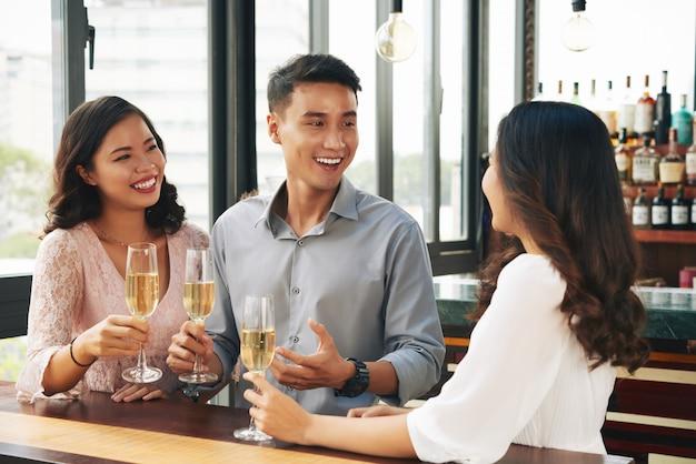 Glimlachende jonge aziatische man en twee vrouwen die met champagne in bar toejuichen Gratis Foto