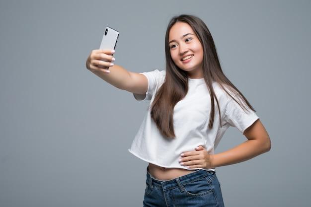 Glimlachende jonge aziatische vrouw die een selfie met mobiele telefoon over geïsoleerde grijze muurachtergrond nemen Gratis Foto