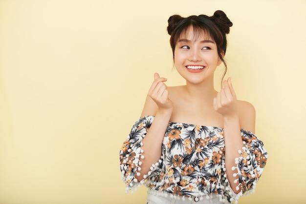 Glimlachende jonge aziatische vrouw in het naakte schouderblouse stellen in studio Gratis Foto