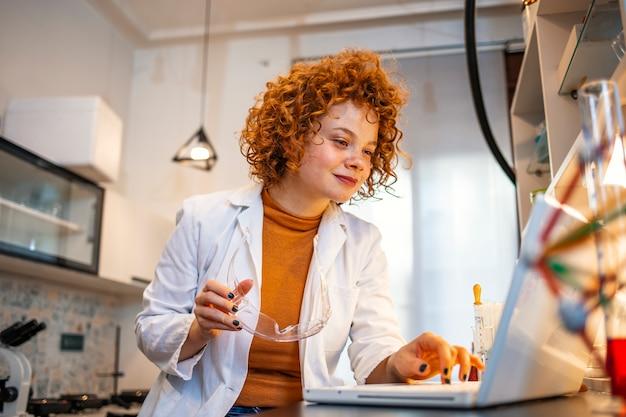 Glimlachende jonge biochemicus die laptop met behulp van bij haar bureau in laboratorium. Premium Foto
