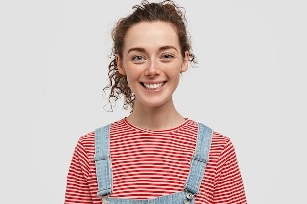 Glimlachende jonge europese vrouw met sproeten met positieve uitdrukking, heeft een vrolijke uitstraling, gekleed in rood gestreepte trui met denim overall, in goed humeur, geïsoleerd over witte muur Gratis Foto