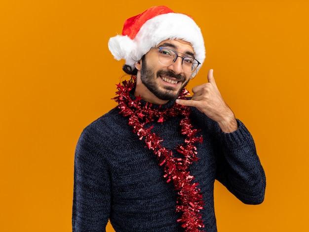 Glimlachende jonge knappe kerel die kerstmishoed met slinger op hals draagt die telefoongesprekgebaar toont dat op oranje achtergrond wordt geïsoleerd Gratis Foto