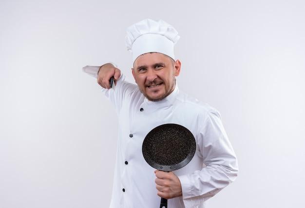 Glimlachende jonge knappe kok in de koekenpan van de chef-kok de eenvormige holding en wijst met mes dat op witte ruimte wordt geïsoleerd Gratis Foto