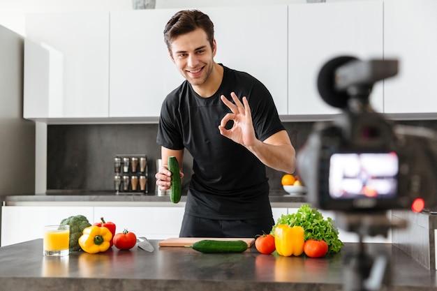Glimlachende jonge man die zijn videoblogaflevering filmt Gratis Foto