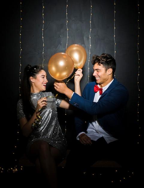 Glimlachende jonge man en vrouw met ballons op bank Gratis Foto