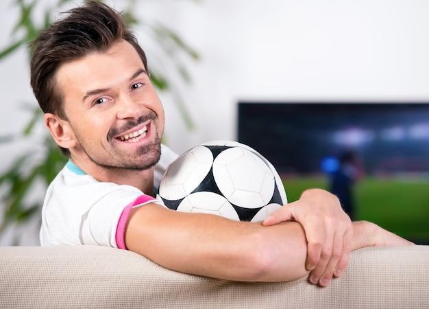 Glimlachende jonge man met voetbal tijdens het kijken naar het spel. Premium Foto