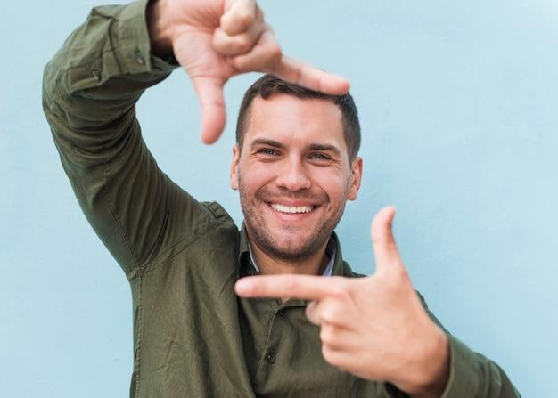Glimlachende jonge mens die handkader over blauwe achtergrond maakt Gratis Foto
