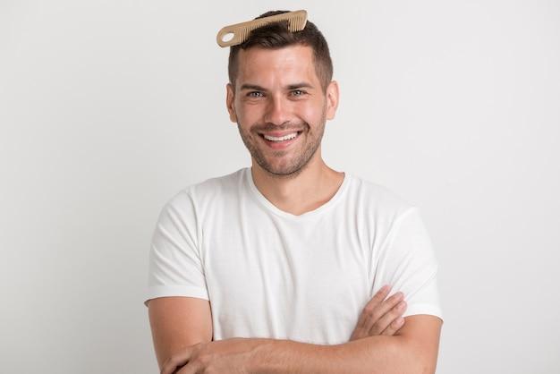 Glimlachende jonge mens die met kam in zijn haar camera bekijkt Gratis Foto