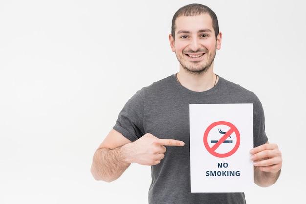 Glimlachende jonge mens die vinger richten naar nr - rokend die teken op witte achtergrond wordt geïsoleerd Gratis Foto