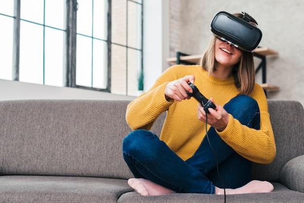 Glimlachende jonge mens die virtuele werkelijkheidsglazen draagt die op bank het spelen videospelletje met bedieningshendels zitten Gratis Foto