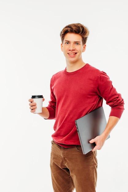 Glimlachende jonge mensenstudent met koffie om en laptop op wit te gaan Premium Foto
