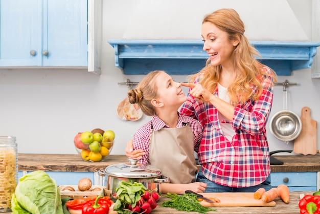 Glimlachende jonge moeder wat betreft de neus van haar dochter met vinger in de keuken Gratis Foto