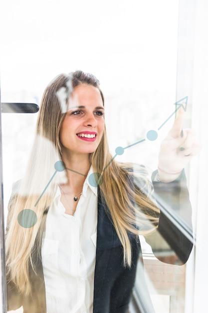 Glimlachende jonge onderneemster die vinger richt op stijgende grafiek op transparant glas Gratis Foto