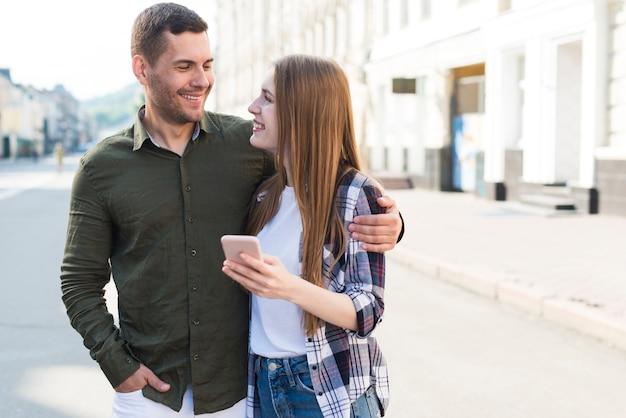 Glimlachende jonge smartphone van de vrouwenholding en het bekijken haar vriend op straat Gratis Foto