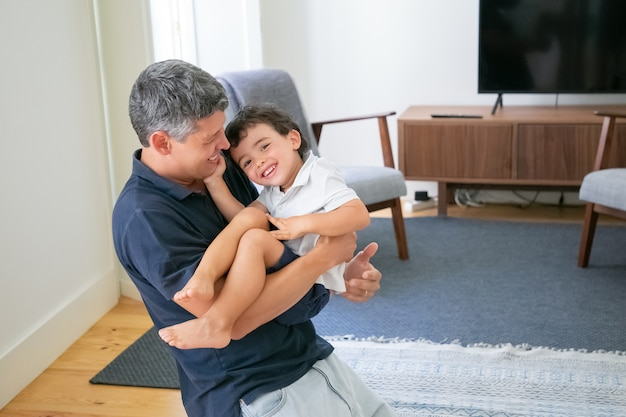 Glimlachende jonge vader die zijn zoon in handen houdt en op knieën in de woonkamer staat. Gratis Foto