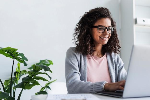 Glimlachende jonge vrouw die bij laptop in bureau werkt Gratis Foto