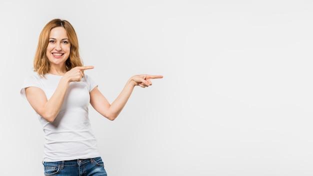 Glimlachende jonge vrouw die de vingers richt die op witte achtergrond worden geïsoleerd Gratis Foto