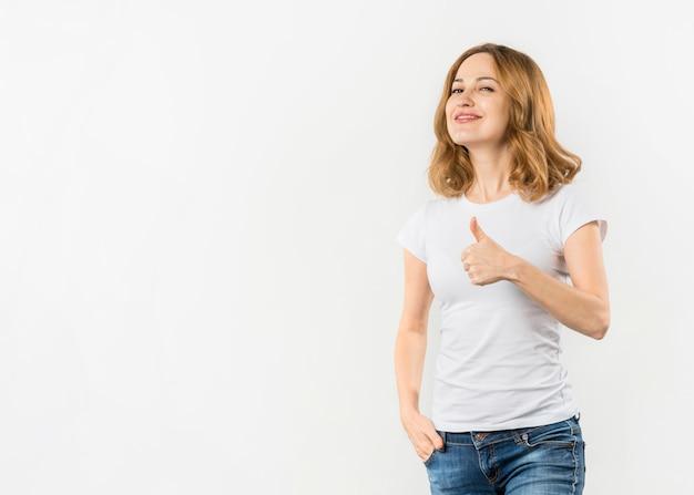 Glimlachende jonge vrouw die duim op gebaar tonen tegen witte achtergrond Gratis Foto