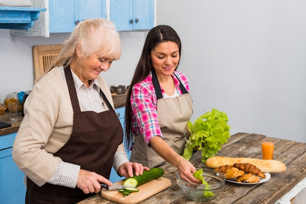 Glimlachende jonge vrouw die haar hogere moeder voor het voorbereiden van salade in de keuken helpen Gratis Foto
